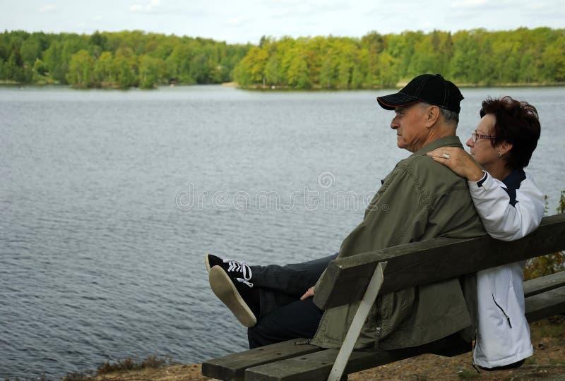 Anziani che riposano su un banco fotografie stock