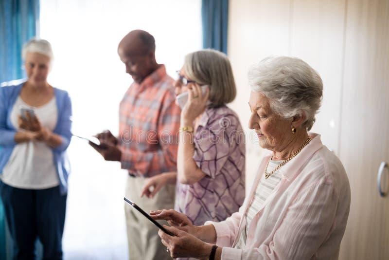 Anziani che usando le tecnologie mentre stando contro la finestra immagine stock