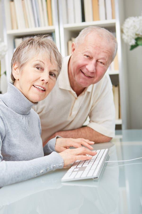 Anziani come coppia con il computer fotografia stock libera da diritti