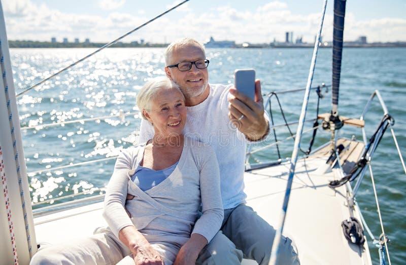 Anziani con lo smartphone che prende selfie sull'yacht fotografia stock libera da diritti