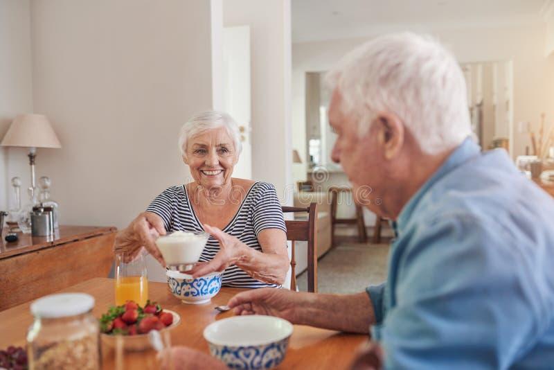 Anziani contenti che mangiano insieme una prima colazione sana a casa fotografia stock