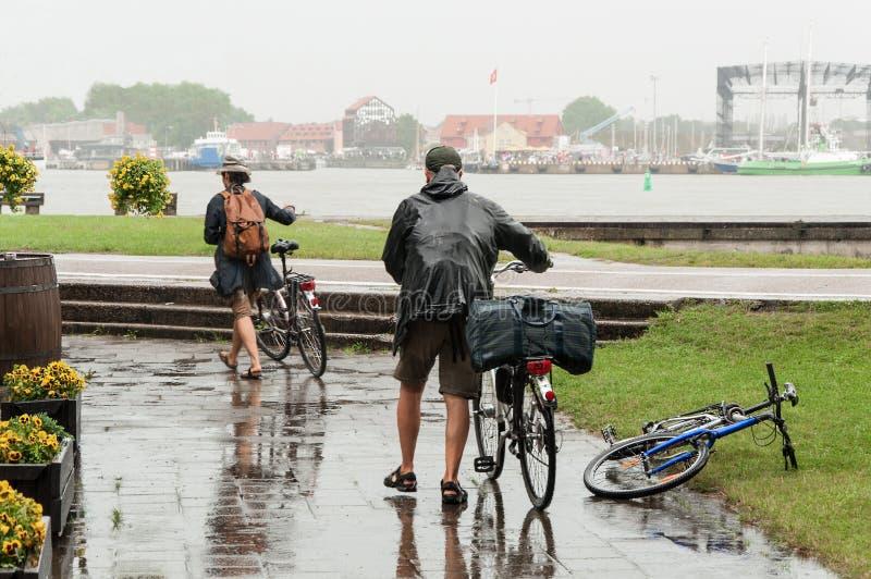 Anziani delle coppie dei ciclisti nel giorno piovoso immagini stock libere da diritti