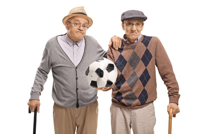 Anziani deludenti che tengono un calcio sgonfiato fotografie stock
