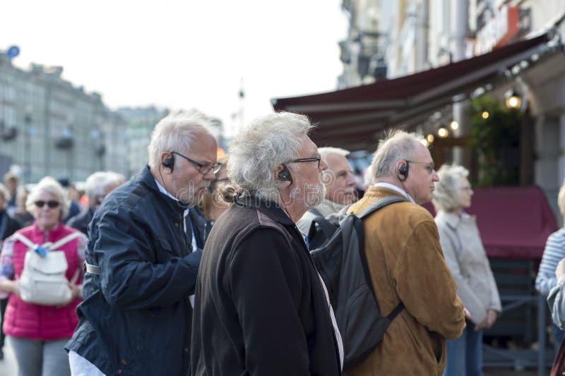 Anziani durante un giro con la guida radiofonica delle cuffie su Nevsky Prospekt St Petersburg, Russia, settembre 2018 immagini stock libere da diritti