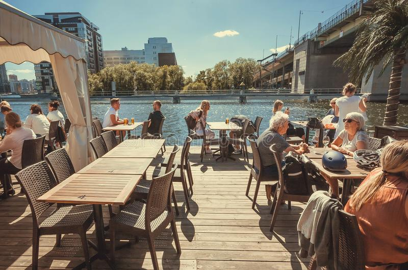 Anziani e giovani cenando al ristorante del fiume vicino al grande ponte concreto fotografia stock