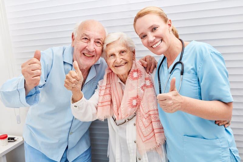 Anziani ed infermiere con i pollici su fotografie stock libere da diritti