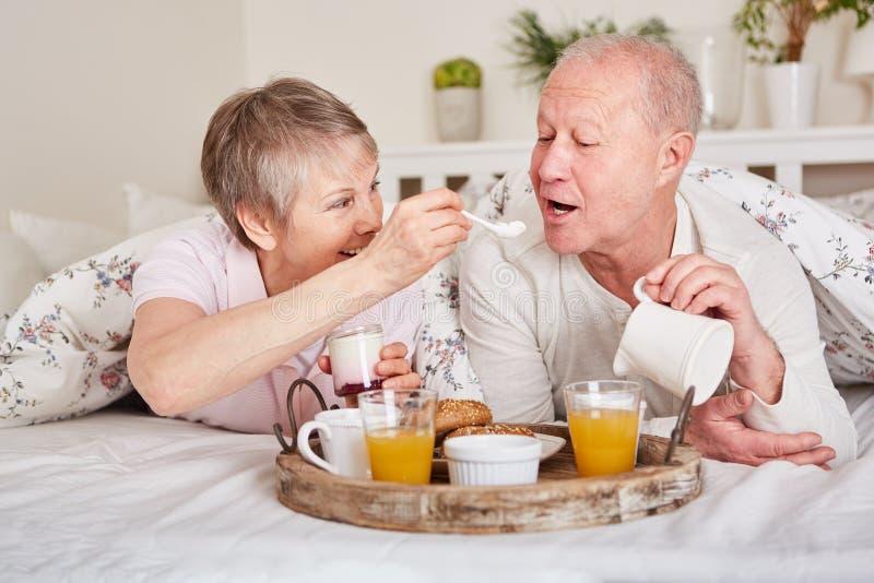 Anziani felici che mangiano prima colazione a letto fotografia stock