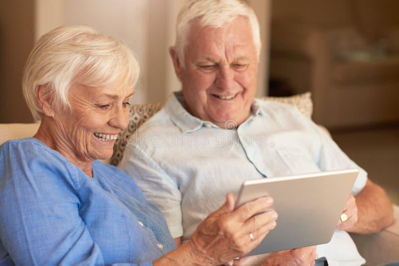 Anziani sorridenti che per mezzo di una compressa digitale sul loro sofà immagini stock libere da diritti