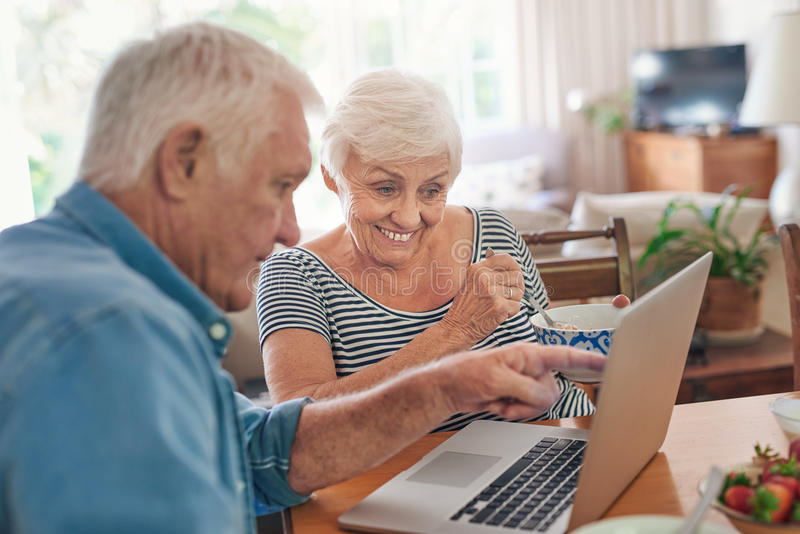 Anziani sorridenti che per mezzo insieme di un computer portatile sopra la prima colazione a casa fotografia stock libera da diritti
