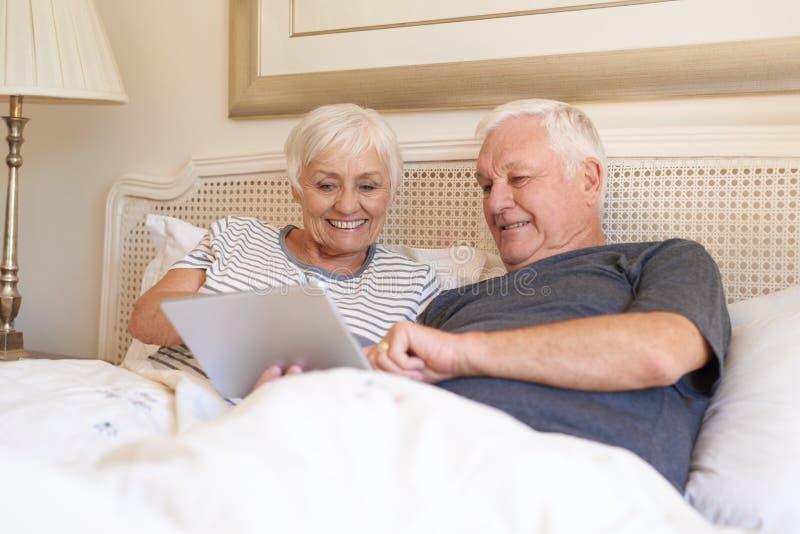 Anziani sorridenti che per mezzo insieme di una compressa digitale a letto immagini stock