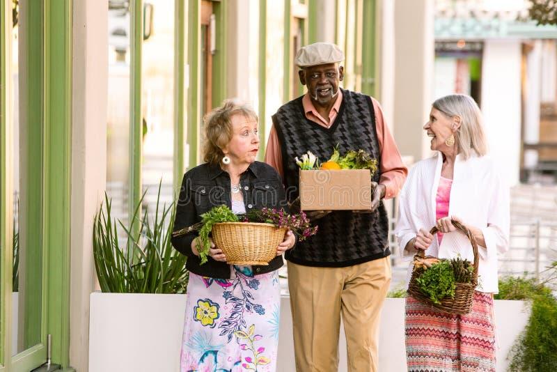 Anziani sorridenti che ritornano dal mercato degli agricoltori fotografie stock