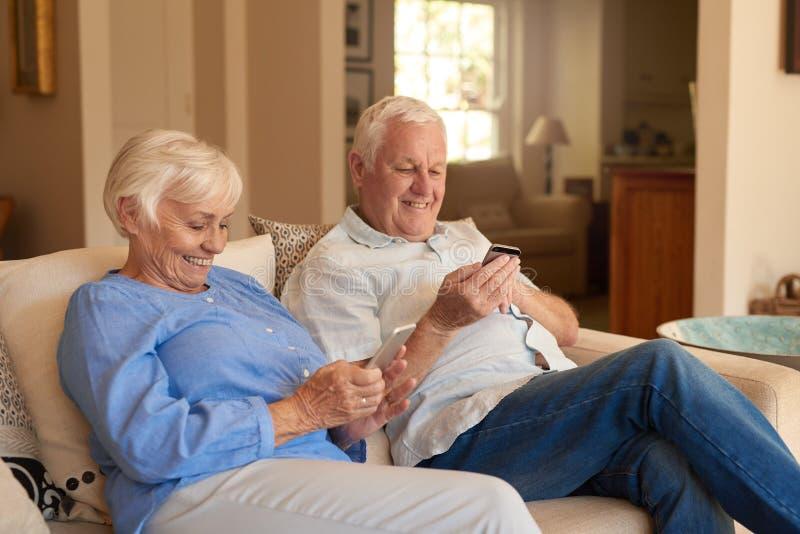 Anziani sorridenti che si siedono su un sofà a casa che legge i messaggi immagine stock libera da diritti