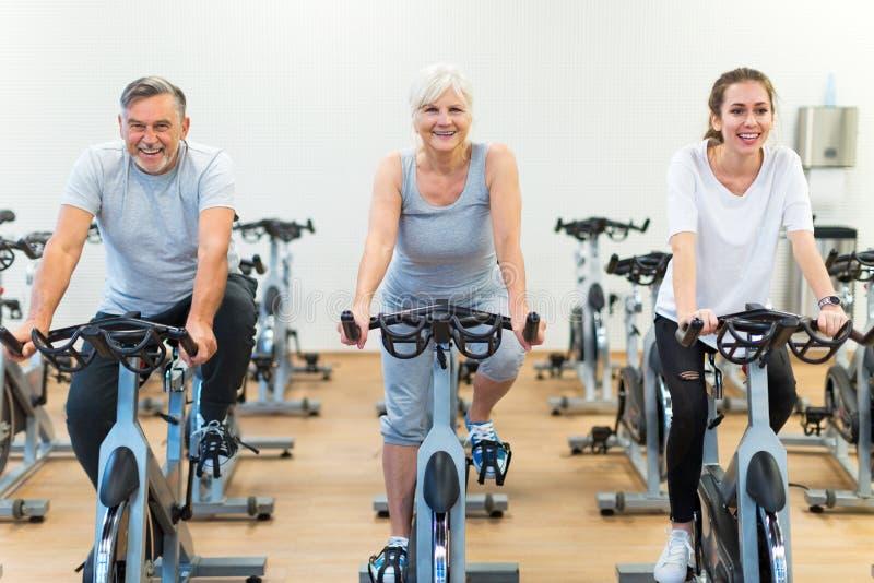 Anziani sulle bici di esercizio nella classe di filatura alla palestra immagine stock libera da diritti