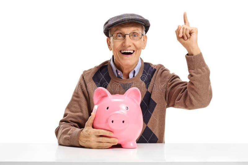 Anziano allegro con il porcellino salvadanaio ad una tavola che indica su immagini stock