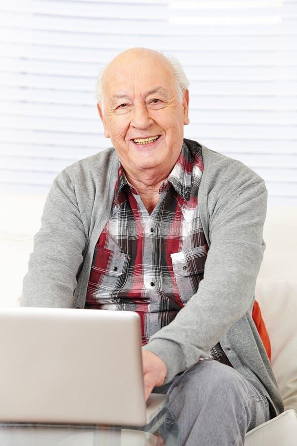 Anziano che lavora con il computer portatile fotografia stock libera da diritti