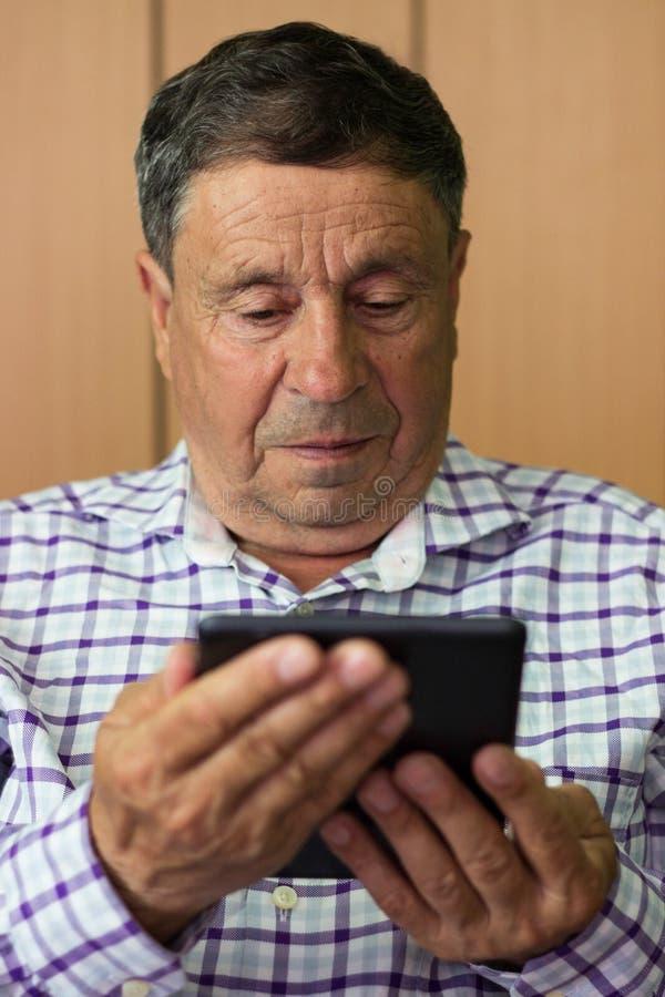 Anziano che per mezzo della compressa digitale moderna immagini stock