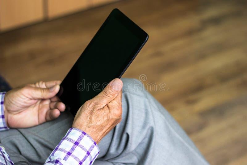Anziano che per mezzo della compressa digitale moderna fotografia stock