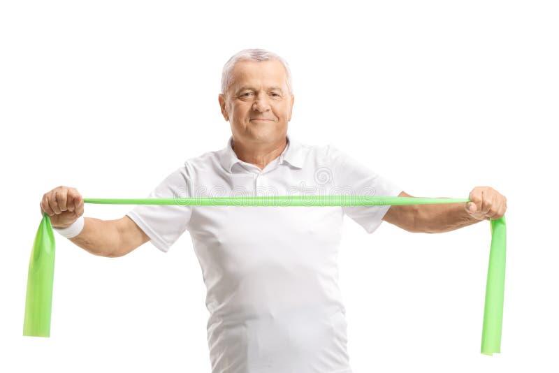 Anziano che si esercita con una banda di gomma fotografie stock