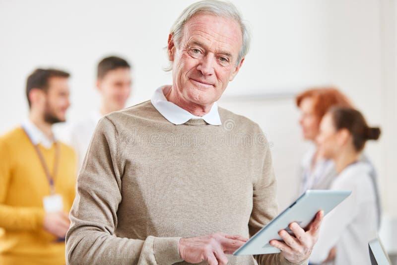 Anziano come consulente con il computer della compressa fotografia stock