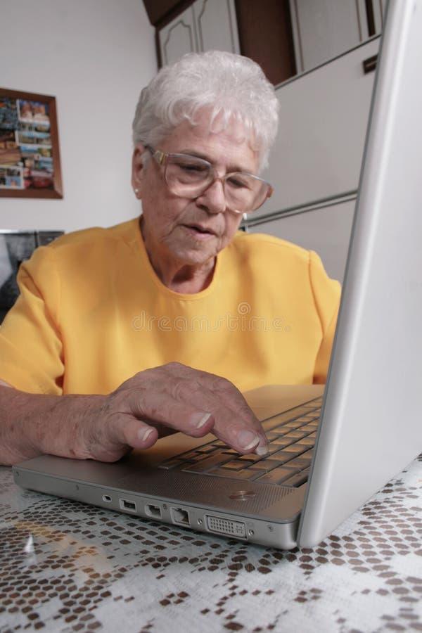 Anziano con un computer portatile immagine stock