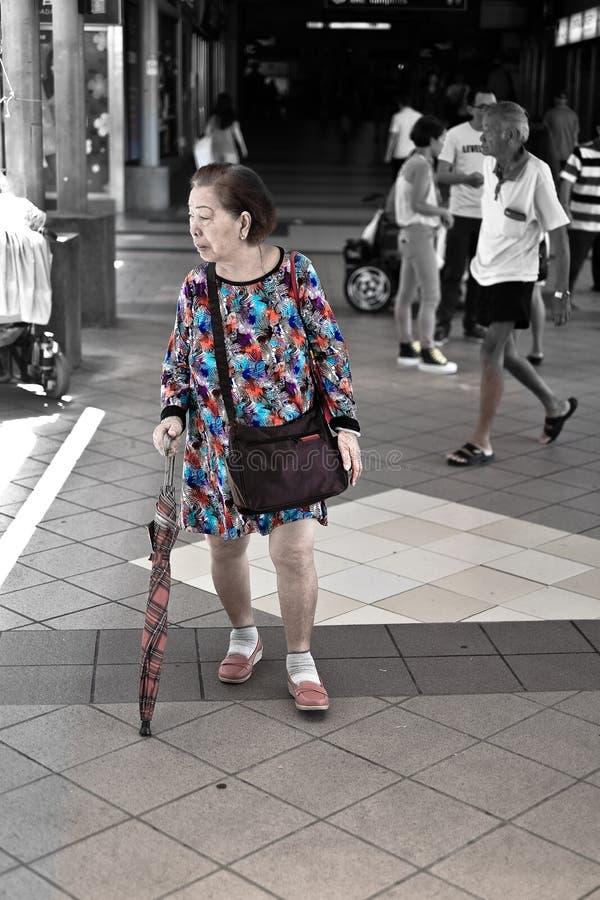 Anziano con un vestito operato, stazione di MRT, Singapore immagini stock