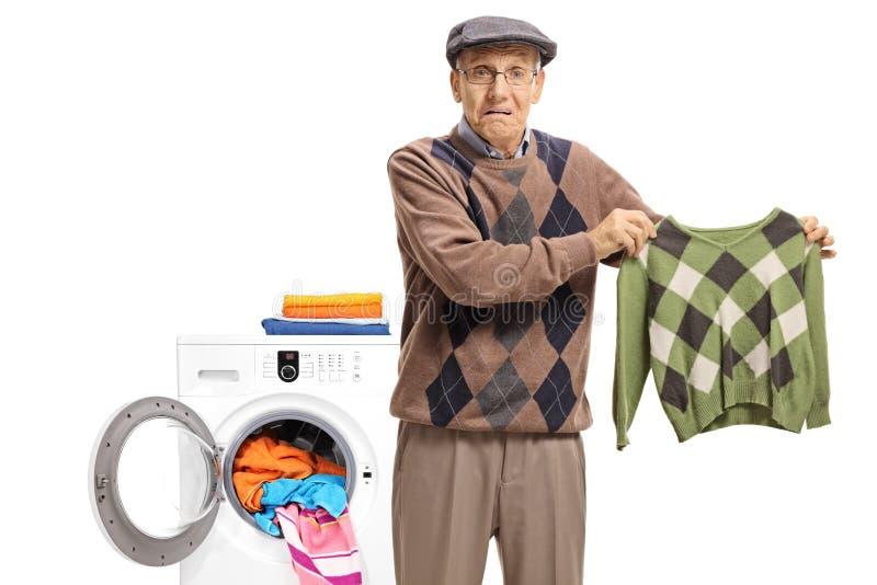Anziano deludente con una blusa restretta davanti ad un lavaggio fotografie stock libere da diritti