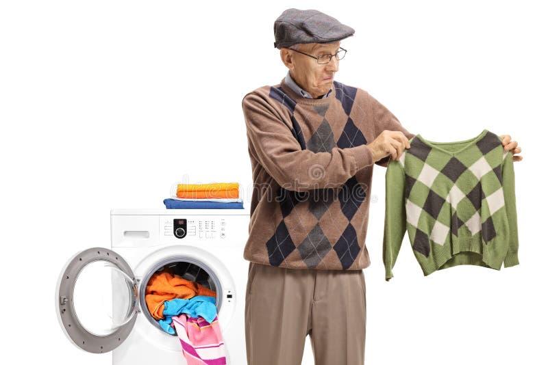 Anziano deludente davanti ad una lavatrice che esamina una s fotografie stock libere da diritti