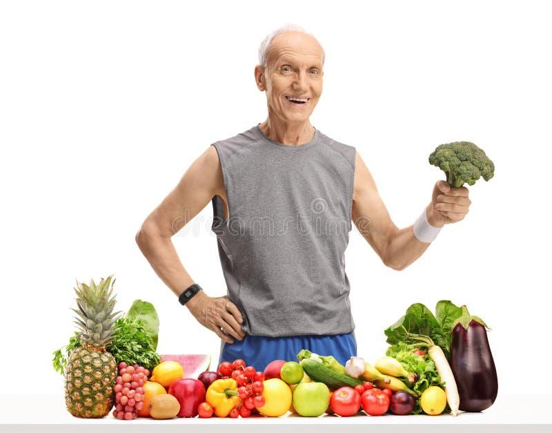 Anziano dietro una tavola con frutta e le verdure che tengono i broccoli immagini stock
