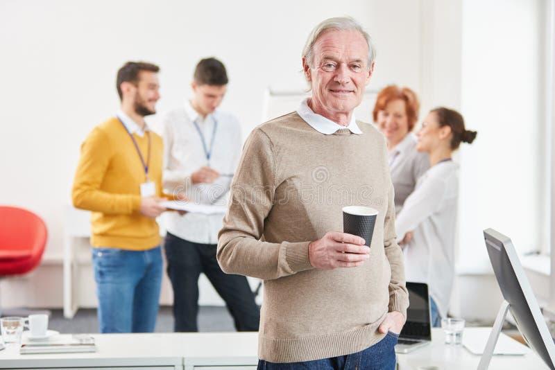 Anziano nella pausa caffè all'ufficio immagini stock libere da diritti