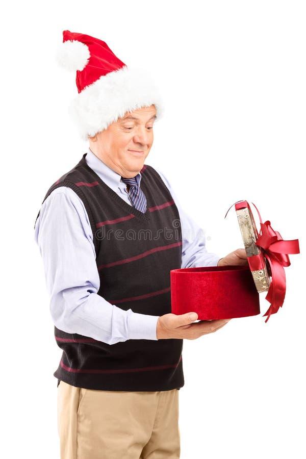 Anziano sorpreso che apre un regalo di Natale fotografie stock libere da diritti