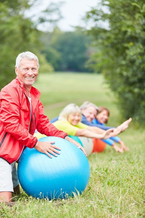 Anziano vitale con la palla di esercizio nel parco fotografia stock