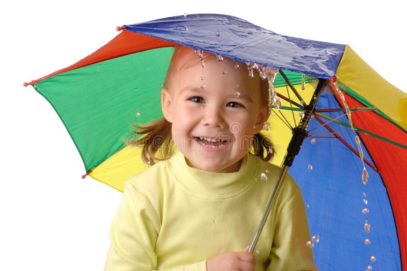 Anziehende Regentropfen des netten Kindes unter Regenschirm stockbild