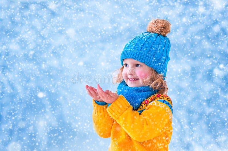 Anziehende Schneeflocken des kleinen Mädchens stockfoto