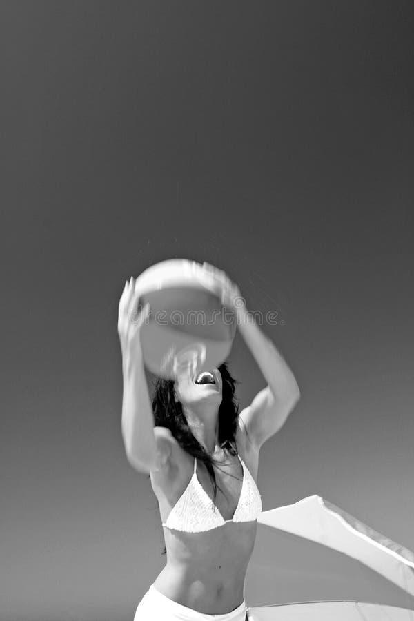 Anziehender Wasserball des Mädchens auf sonnigem Strand in Spanien. Schwarzweiss. lizenzfreie stockfotografie