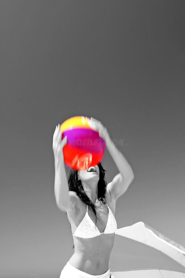 Anziehender Wasserball des Mädchens auf sonnigem Strand in Spanien. Schwarzweiss mit Kugel in der Farbe. lizenzfreie stockfotos