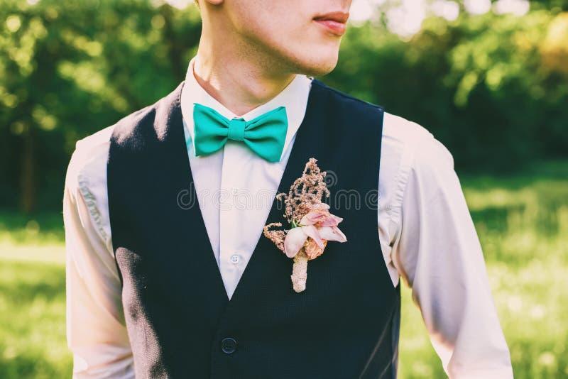 Anzug des Bräutigams mit Fliege und Boutonniere stockfoto