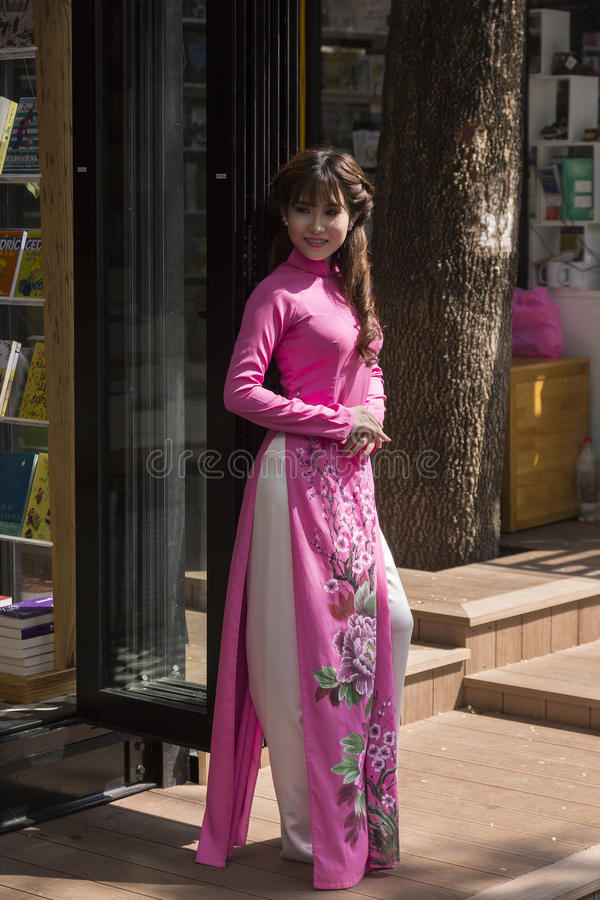 Ao Dai Vietnamese national dress. The áo dài is a Vietnamese national costume, now most commonly worn by women. In its current form, it is a tight-fitting stock photography