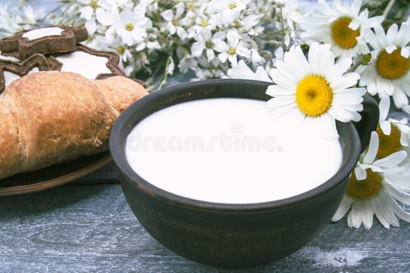 Ao lado dos croissant e das margaridas ? um copo do leite fotografia de stock royalty free