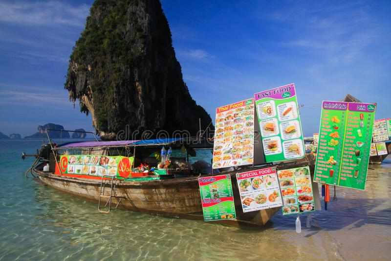 AO NANG甲米府,泰国- 1月3 2017年:在被隔绝的岩石的看法在有长尾巴小船的安达曼海在浅水区卖 免版税库存图片