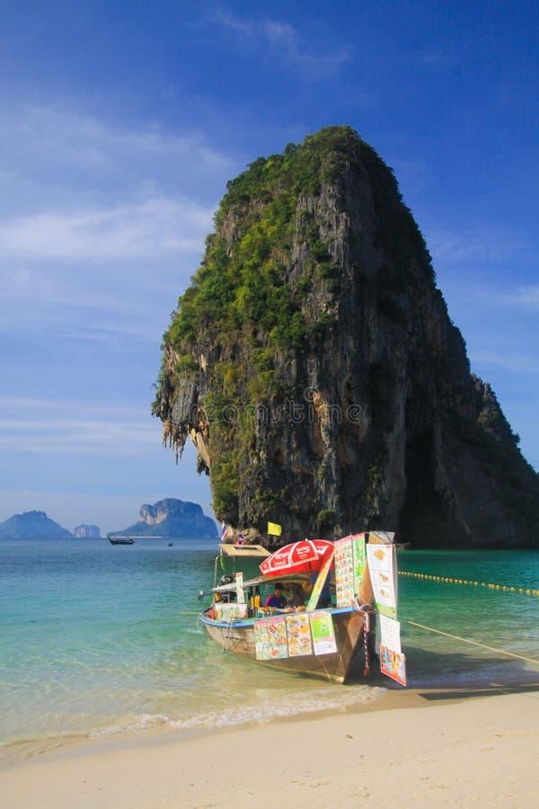AO NANG甲米府,泰国- 1月3 2017年:在被隔绝的岩石的看法在有长尾巴小船的安达曼海在浅水区卖 库存照片