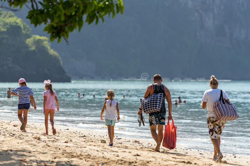 Family vacations on beach. Parents with children walk along sea on beach royalty free stock photos