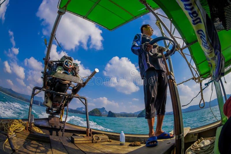 AO NANG, THAILAND - FEBRUARI 09, 2018: Utomhus- sikt av den oidentifierade mannen som behandlar en fartygmotor med en suddig natu arkivbilder
