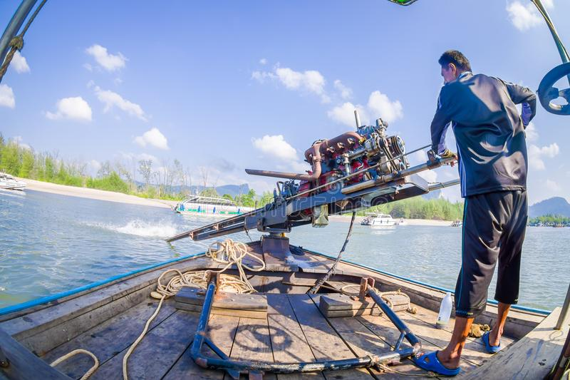 AO NANG, THAILAND - FEBRUARY 09, 2018: Close up of unidentified man manipulating a boat motor with a blurred nature royalty free stock images