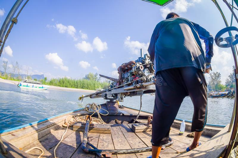 AO NANG, THAILAND - FEBRUARY 09, 2018: Unidentified man manipulating a boat motor with a blurred nature background stock photos