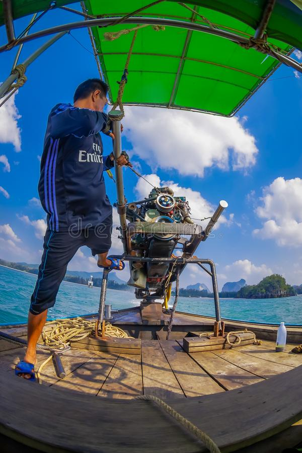 AO NANG, THAILAND - FEBRUARY 09, 2018: Unidentified man manipulating a boat motor with a blurred nature background royalty free stock photos