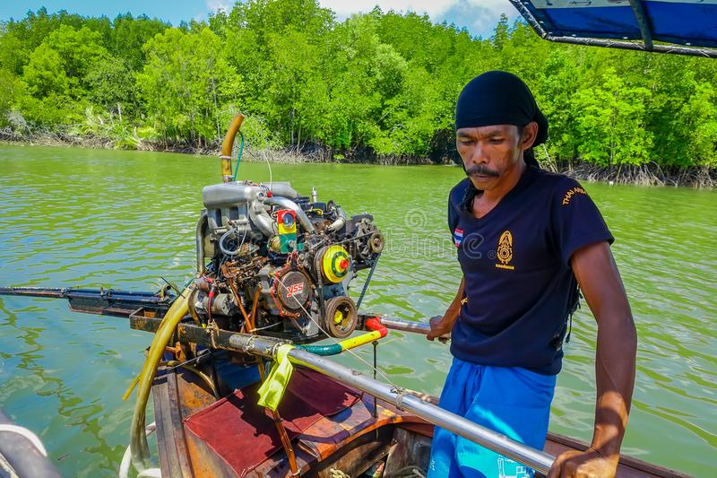 AO NANG, THAILAND - FEBRUARY 09, 2018: Unidentified man manipulating a boat motor of long fisihng boat with a nature stock image
