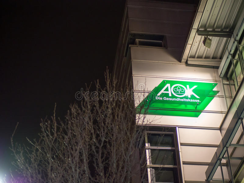 AOK at night. Sign on a building of the german AOK health insurance during night time - copy space to the left royalty free stock photography