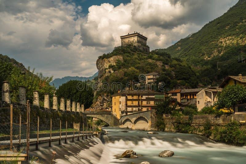 Aosta gammal stenslott med floden i norr Italien royaltyfria foton