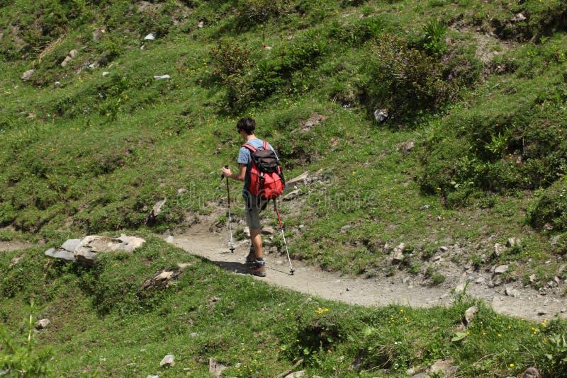 ` Aosta, Italia de Val d, el 5 de julio de 2018: adolescente masculino que camina solamente en un ensayo de la montaña imagen de archivo libre de regalías