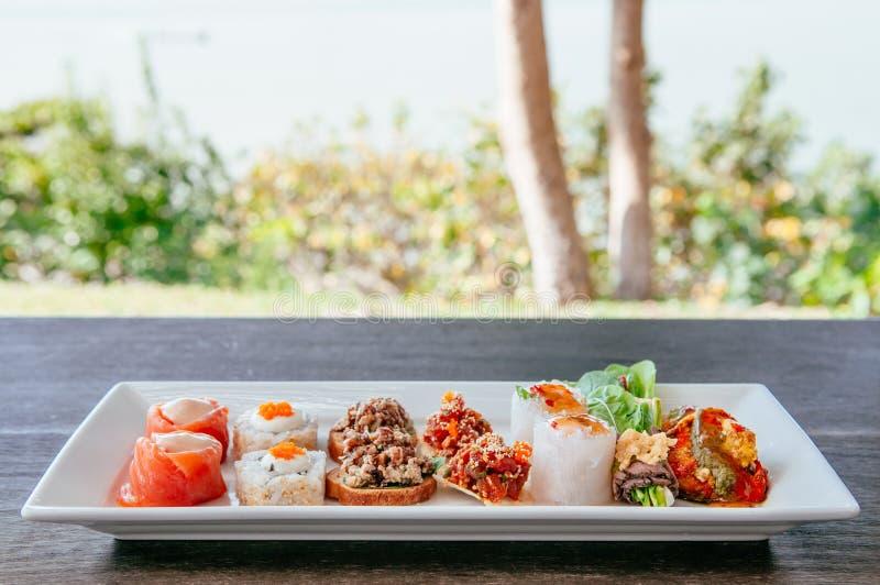 Apéritif asiatique de canapes - saumon fumé, maki, larb, tartre de thon images stock